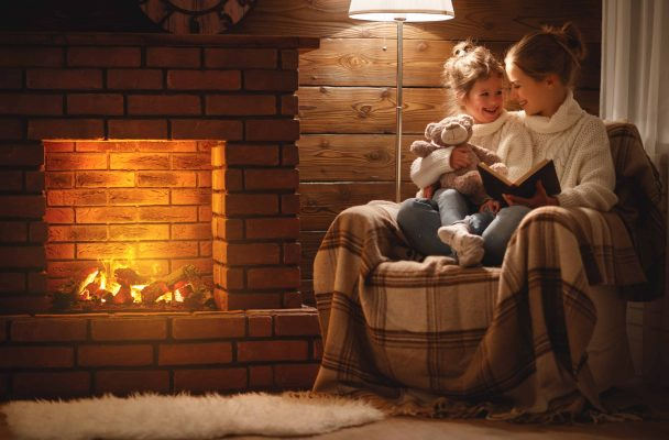 happy family mother and child daughter read book on winter evening near energy efficient fireplace