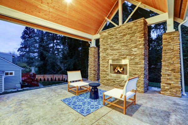 Chic covered back patio with built in gas fireplace